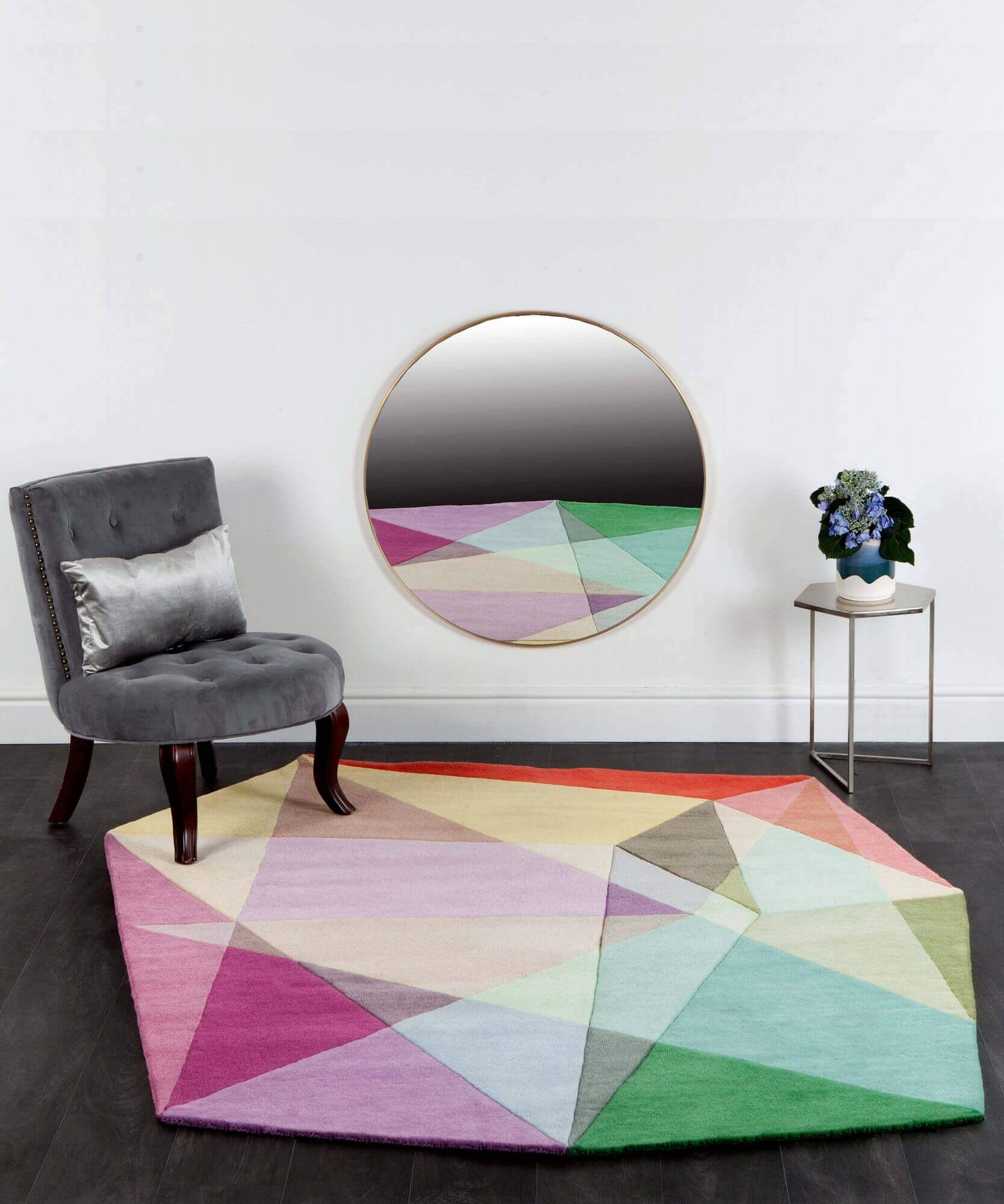 Sonya Winner Prism Pastels diamond rug in a modern design setting with Roce Bobois grey velvet cocktail chair, showcasing the irregular geometric pattern and soft green, pink and yellow colours of the handmade, natural designer rug