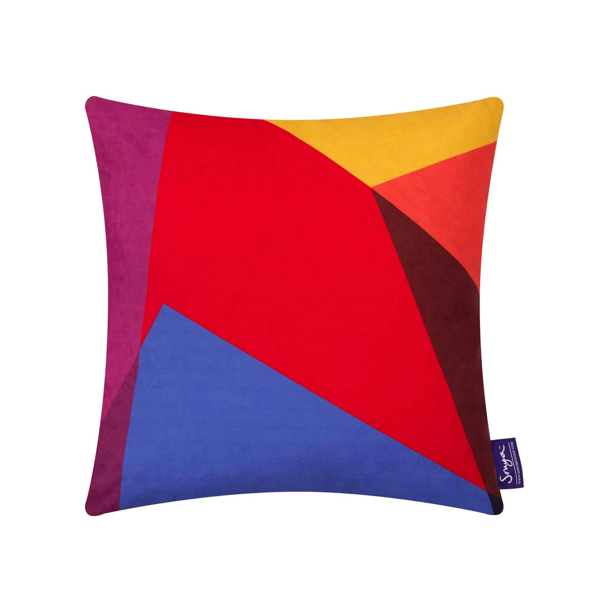 A cropped detail image of the colourful Sonya Winner After Matisse Harlequin cushion, showcasing the bright blue, red, yellow and pink colours, playful pattern and rich texture