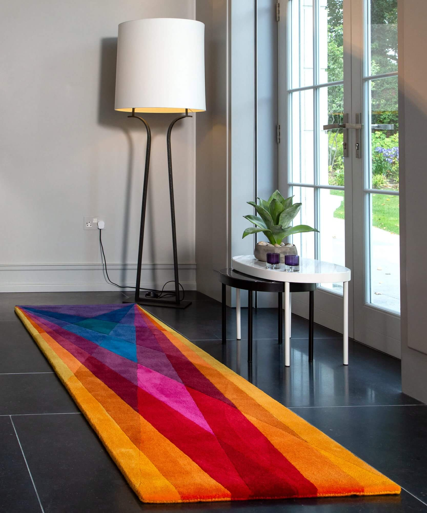 Sonya Winner Rainbow multi coloured runner rug shown in a large entrance hall, with John Lewis black and white marble coffee table and white floor lamp, showcasing the modern geometric pattern and brightly coloured runner rug