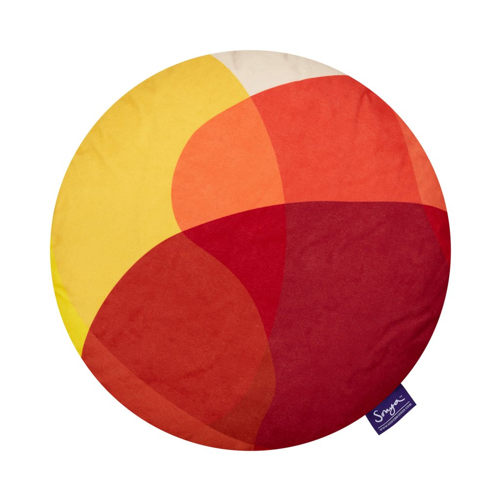 A cropped detail image of the Sonya Winner Jellybean Mango cushion, showcasing the bright red, yellow and orange colours, the geometric pattern and luxurious faux suede texture